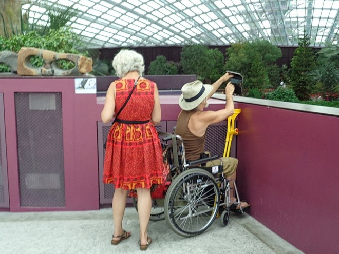 Shows a man in a wheelchair in front of a half wall on a raised section. He cannot see over to the ground below. He is taking a picture with his mobile phone and can also use it to see something of below.