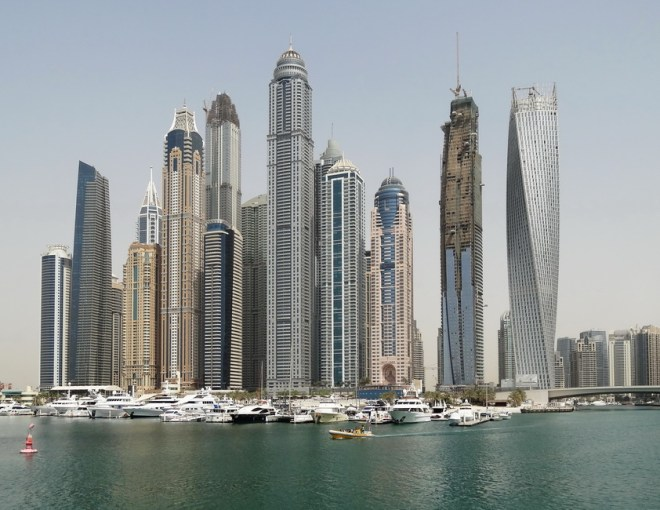 Picture of towering buildings in the Dubai skyline with river in the foreground