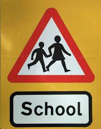 A triangular sign with a red border and the outline of two children running holding hands. The word school is written underneath.