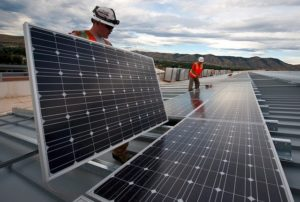Two men in hard hats are installing solar panels.