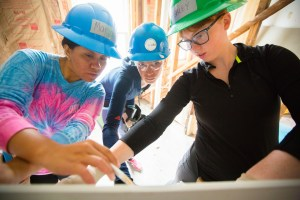 Picture of three young women wearing hard hats and holding pens and looking at a drawing on a table top