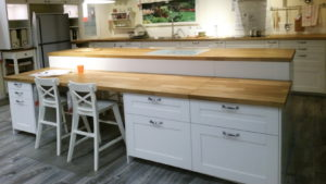 Picture shows a long island bench with white drawer cupboards and a timber benchtop. It has a low section attached to the front of the bench with a knee hole with two child sized bar stools. The knee space could just as easily suit a wheelchair user