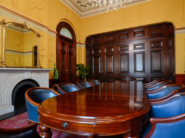 Picture of the Treasury Room at Sydney Town Hall showing heritage values and a large wooden table with blue seats around like a board table