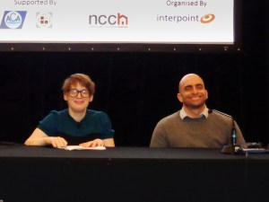 Kelly Vincent and Paul Nunnari sit behind a table on the stage ready for the Panel session