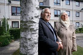 picture of Habinteg's report with two older people standing by a tree against a block of units in the background