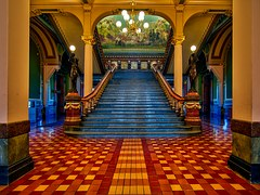 Grand staircase in a heritage building showing a blue carpeted staircase and a mural at the top of the flight.