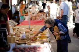 A woman holding a baguette is reaching across a market stall