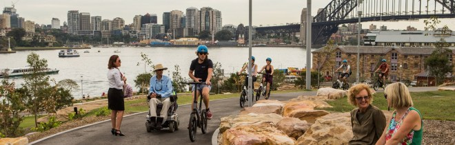 Landscape view of Barangaroo Parkland showing a pedestrian, wheelchair user, cyclist and pram pusher. Mentioned in EU tourist guide.