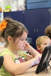 young girl in a classroom setting looking at an iPad