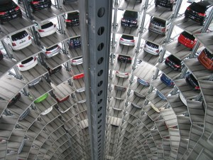 A view looking down a long vertical tunnel with cars parked in racked bays
