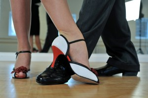 The feet of two dancers. The woman is wearing red and white shoes and the man regular black shoes