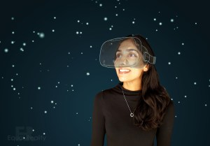 Against a dark starry background a young woman in a dark top looks upwards through transparent goggles