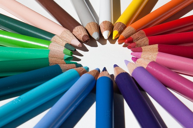 lots of coloured pencils are laid out in a circle with the tips pointing to each other so they make a circle of their points