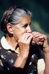 An older woman is eating a large sandwich. She is wearing a brown dress with a cream collar