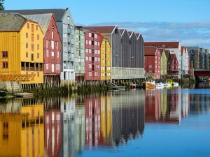 Tall houses are reflected in the water.The houses are different colours, yellow, red and blue