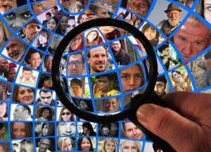 A magnifying glass is held over a grid montage of human faces