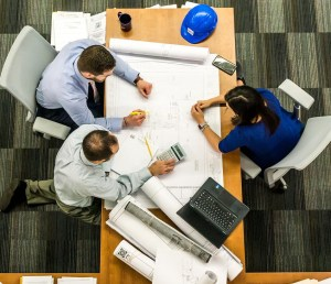 aerial view of three people at a desk looking at a set of construction drawings. Diversity and Inclusion Design Studio.