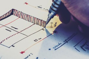 Close up of a pen drawing with the tip of the pen showing as drawing a line