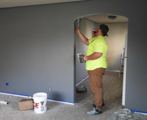 A man in a bright yellow T shirt is painting and archway in a wall inside a home. The wall is grey and there are tools on the floor. Accessible housing, costs and gains.