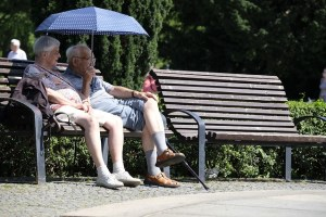 An older man and woman sit on a wooden slatted park bench. The man is holding a blue umbrella to shade from the sun. There is another empty bench next to them. They are sitting alongside the path and there are trees behind them.