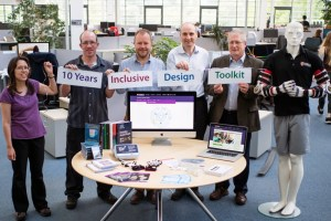 five members of the inclusive design group stand behind a table with the toolkit displayed. Each person is holding a card with a word. The words spell out 10 years inclusive design toolkit.