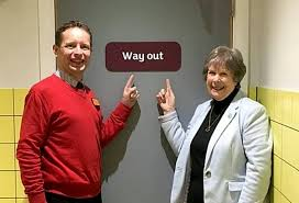 A man in a red pullover, and a woman with a white jacket stand in front of a door that has a way out sign on it.