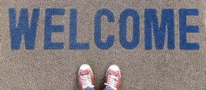 A mid grey doormat viewed from above with the word welcome in blue. At the bottom of the picture you can see the tops of a pair of red and white sneakers.