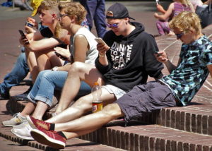 four young people sit on brick steps. Three of them are looking at smartphones. There are three young men and one young woman. It looks like summer as the men are wearing shorts.