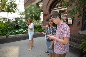 Three young people wearing headsets are looking at their smartphones in an outdoor setting