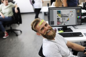A bearded man in a white shirt leans back from his desk and computer. He is laughing and has a sticker on his forehead that reads, be happy.