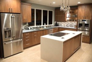 Picture shows a kitchen in timber tones. There is an island bench with an induction cooktop. Drawers replace cupboards. Universal design in the kitchen.