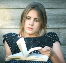 Girl sits with a book flicking pages and looking a little unhappy.