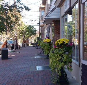 brick paved footpath with planter boxes with flowers .