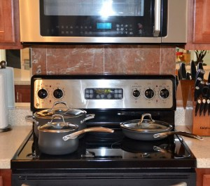 kitchen stove with three pans and a panel at the rear with knobs. Above you can see the bottom of a microwave with reflected glare on the door.