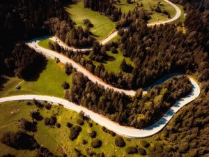 An aerial view of a winding road through a wooded area.
