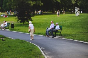 An older woman walks on a bitumen path in a park. Two older men are sitting on a seat along the pathway.