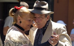 Close up of an older man and woman with their heads together dancing. He is wearing a hat and cravat, and she is wearing a red flower in her hair. They look loving.