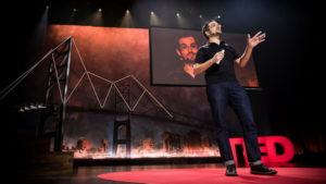 Johan Carey in jeans and black polo shirt is on the stage at a Ted Talk