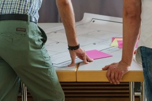 A desk with a large sheet of paper and pink post it notes. A person stands with their hand resting on the table. Inclusive design is more than a checklist.