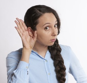 A woman with dark hair wearing a light blue shirt holds her right hand up to cup her ear to indicate she is trying to hear something