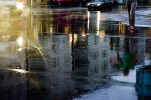 A wet roadway with reflections of traffice and buildings and a person's legs walking