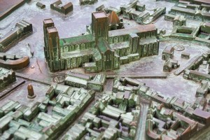 A metal model showing a town layout in relief with Braille on buildings and streets. There is a church and lots of houses and a town square represented.