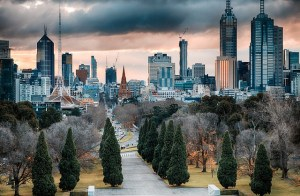 A distant view of Melbourne city buildings. In the foreground is a wide footpath with trees either side