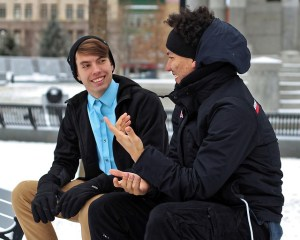Two young men sit on a bench outside and are in conversation