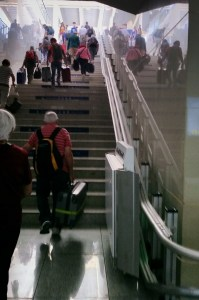 People are carrying heavy luggage up 56 steps at a train station. A platform lift remains folded at the bottom of the steps.