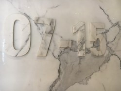 A grey marble wall has numbers embossed on it. It is difficult to see unless there is shadow on the embossing.