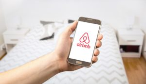 A hand is holding a smartphone with an Airbnb red logo on white background. In the background is a double bed.