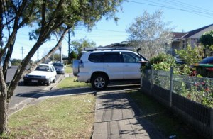 A white SUV is parked across the footpath nosing into a driveway