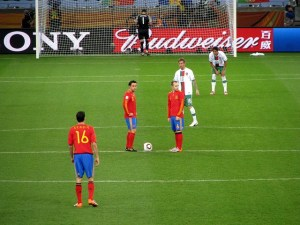 Five football players stand waiting for play to start. Three are dressed in red and blue, two in white and the goalkeeper in black. The grass is very green