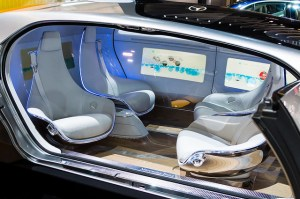 Internal view of a driverless car showing seats facing both back and forward.